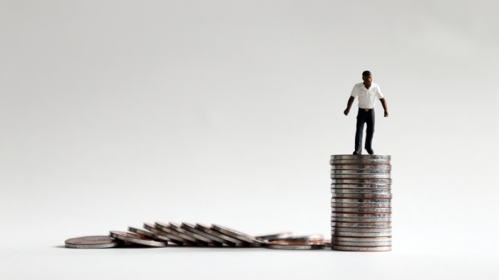 The concept of social status improvement for blacks. A miniature black man standing in a pile of coins.